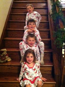 Four kids are sitting on stairs.