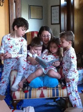 Woman reads to four kids in matching pj's